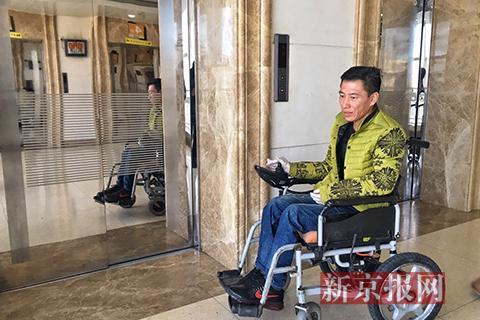 宋学文坐在轮椅上等待电梯。新京报记者 王飞 摄