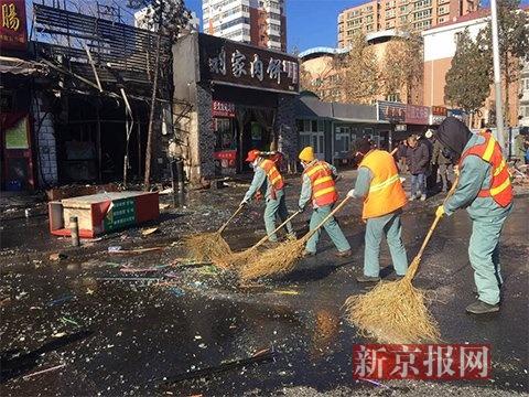 环卫工正在清算爆燃时散落的玻璃碎片。 新京报记者 王飞 摄