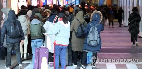资料图片:2017年12月5日上午,在首尔中区的乐天免税店门前,游客一大早就开始在严寒中排队等待进入免税店。(韩联社)