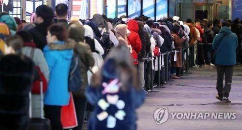 材料图片:2017年12月5日,在首尔市区某免税店门口,主顾排起长龙。(韩联社)