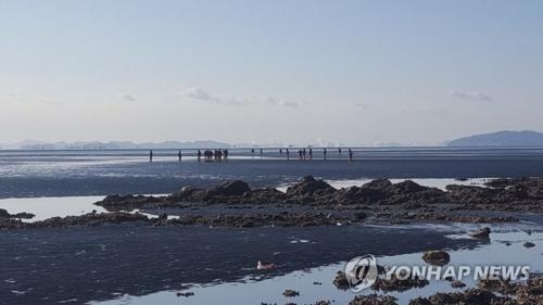 12月5日上午,在仁川市灵兴岛一海水浴场南侧滩涂,海警发现事故钓鱼船船长吴某遗体。(图片来源:韩联社)