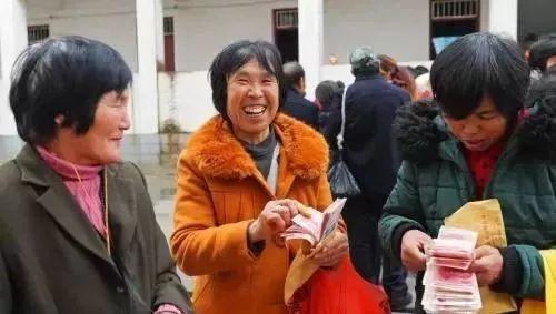 ↑资料图:农民工领到工资后很高兴。(来源:中国新闻网)