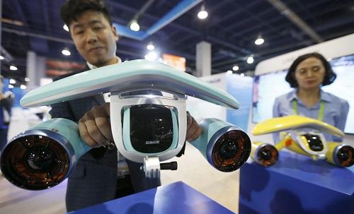 1月10日,在美国拉斯维加斯,中国深之蓝公司工作人员在消费电子展上展示一款游泳推进器。使用者可握住推进器上的扶手,通过两侧螺旋桨产生的推力在海里畅游。新华社记者李颖摄