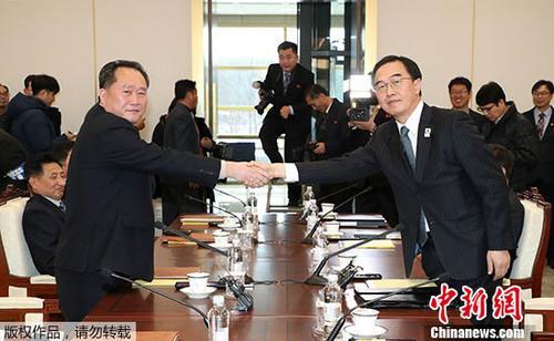 """2018年1月9日,韩方代表团团长、统一部长官赵明均(右)和朝方代表团团长、朝鲜祖国和平统一委员会委员长李善权在板门店韩方一侧""""和平之家""""握手。"""