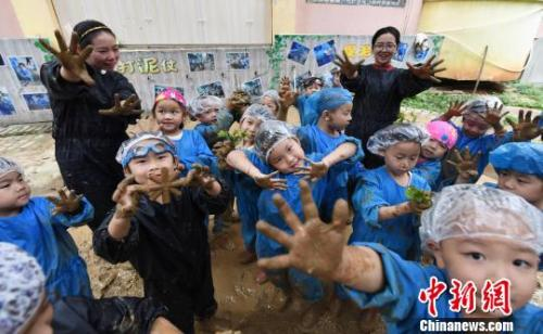 资料图:江西省新余市蓓蕾幼儿园大一班的孩子们在老师带领下抓泥鳅、打泥仗。 赵春亮 摄