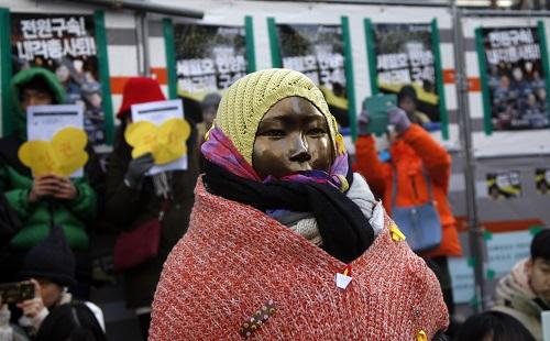 """资料图:在韩国首都首尔,民众为""""慰安妇""""少女像戴上帽子和围巾。新华社记者姚琪琳摄"""