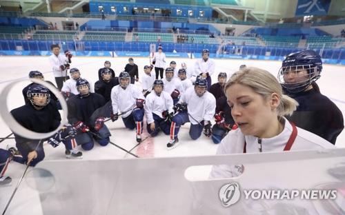 2月7日下午,在江陵市关东冰球中心,韩朝女子冰球联队主教练萨拉·穆雷(右一)给队员讲解战术。(图片来源:韩联社)