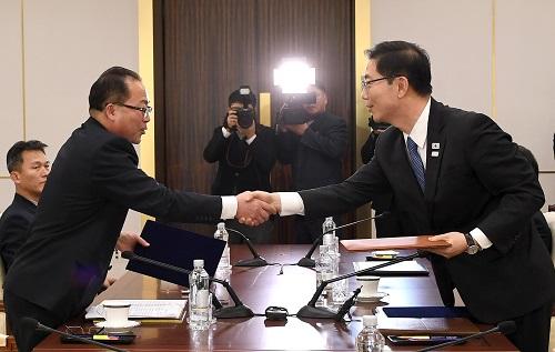 """1月17日,在板门店韩方一侧的""""和平之家"""",朝方代表团团长、朝鲜祖国和平统一委员会副委员长田钟秀(左)与韩方代表团团长、韩国统一部副部长千海成握手。新华社发"""