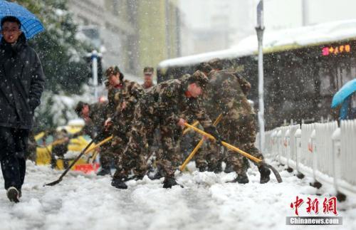 1月4日,江苏驻地边防总队机关勤务保障大队组织80多名官兵走上街头,铲除积雪,确保群众顺利出行。 中新社发 章善玉 摄 图片来源:CNSPHOTO