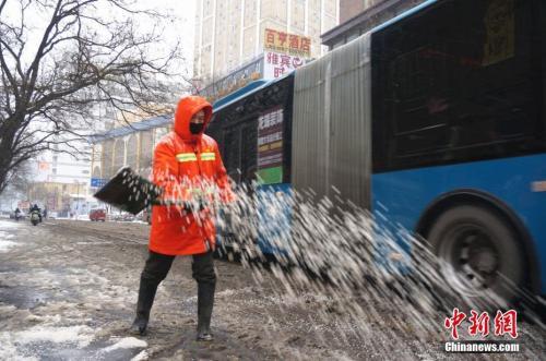 1月4日凌晨3点郑州市的环卫工人们就到岗除雪。图为环卫工人在街头撒融雪剂。 韩章云 摄