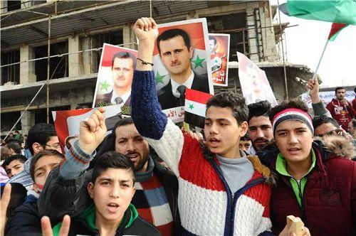 2017年12月21日,在叙利亚阿勒颇,民众手举叙利亚总统巴沙尔头像,纪念阿勒颇解放一周年。新华社发(阿马尔摄)