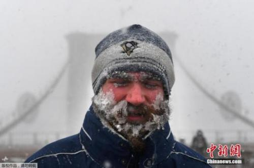 资料图:纽约布鲁克林大桥上,一名行人行走在漫天暴雪中,脸上布满冰碴。