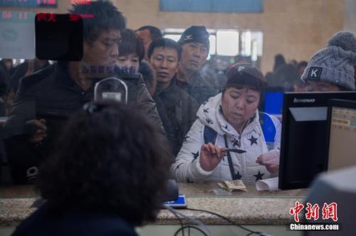 资料图:1月4日,山西太原火车站,旅客在人工售票窗口买到出行的火车票。 中新社记者 韦亮 摄