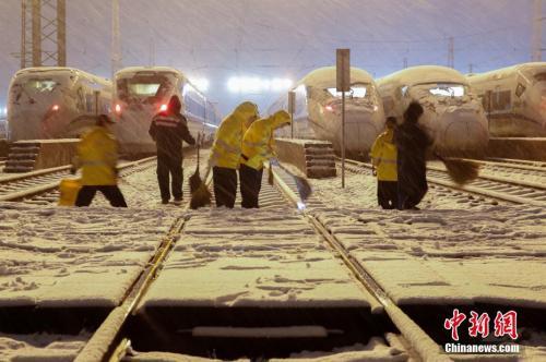1月25日晚,在上海动车段南翔动车运用所,机械师们正加班加点,对高铁列车进行除冰融雪作业。张亨伟 摄