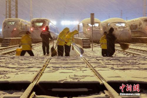 资料图:1月25日晚,上海动车段南翔动车运用所,机械师们正加班加点,对高铁列车进行除冰融雪作业。张亨伟 摄