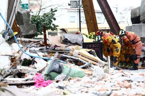 """花莲县长傅昆萁11日表示,剩余两名失联大陆游客确定罹难,将停止搜救,家属也同意进驻大型机具开挖,搜救人员撤离前对云门翠堤大楼鞠躬。图片来源:""""中央社"""""""
