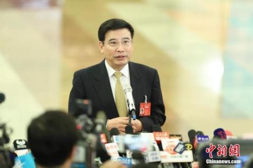 """3月5日,十二届全国人大五次会议在北京人民大会堂开幕。工业和信息化部部长苗圩在""""部长通道""""接受采访。中新社记者 盛佳鹏 摄"""