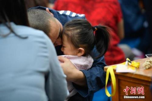 资料图:一名服刑人员亲吻怀里的女儿。中新社记者 刘冉阳 摄