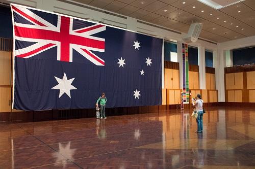 资料图片:民众在澳大利亚联邦议会大厦宴会大厅内悬挂的巨幅国旗前留影。新华社发