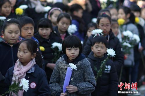 12月10日,在第四个国家公祭日来临之际,参加过当年战争的抗战老兵、侵华日军南京大屠杀遇难者家属、南京1213志愿者联合会的志愿者们来到南京光华门遗址公园,向这片曾经发生过激烈战斗的阵地献上和平岁月里的悼念菊花,祈祷永远和平。 中新社记者 泱波 摄