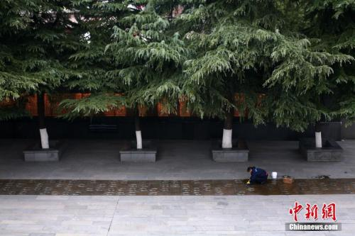 12月7日,侵华日军南京大屠杀遇难同胞纪念馆内的工作人员擦拭幸存者脚印铜板路。中新社记者 泱波 摄