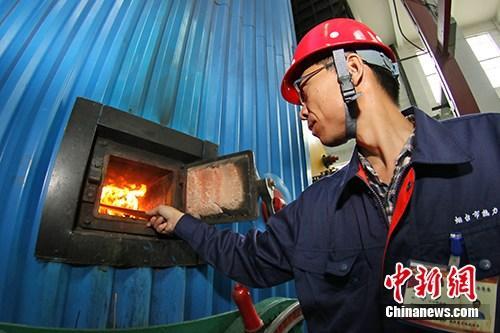 资料图:燃煤供热站点火烘炉。中新社发 唐克 摄
