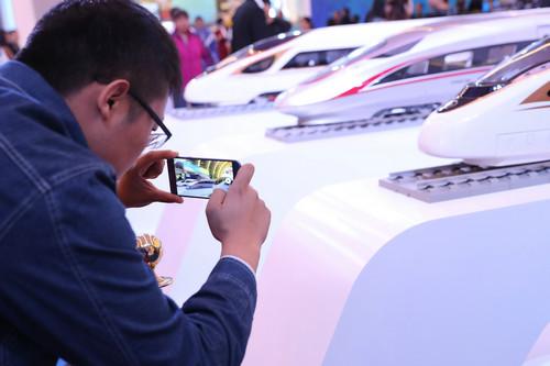 """资料图片:10月12日,一名观众在""""砥砺奋进的五年""""大型成就展现场拍摄""""复兴号""""列车模型。新华社记者 张玉薇 摄"""
