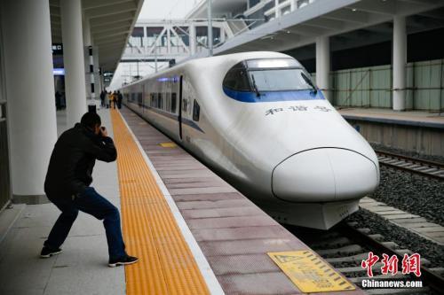 """资料图:2017年12月27日,记者在贵阳北站登上了开往重庆的""""试跑""""动车,提前体验渝贵铁路即将带来的快捷和便利。中新社记者 贺俊怡 摄"""