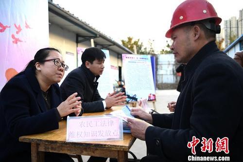 资料图:法律工作者为外来务工人员提供法律咨询。中新社记者 韩苏原 摄