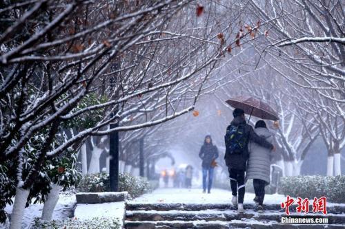 """1月3日,西安迎来今年的第一场降雪,纷飞的雪花使整个古城""""银装素裹"""",当地民众乐赏美丽雪景。王晓凯 摄"""