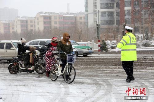 1月4日,山东省枣庄市公安局市中分局交通警察大队民警在当地的西外环路上冒雪指挥交通。 中新社发 吉 �� 摄 图片来源:CNSPHOTO