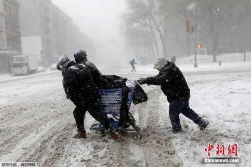 """图为曼哈顿""""上城区""""的居民在暴雪中艰难出行。"""