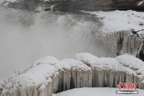 陕西延安黄河壶口瀑布一片银装素裹,瀑布两岸被积雪笼罩。梁鹏 摄