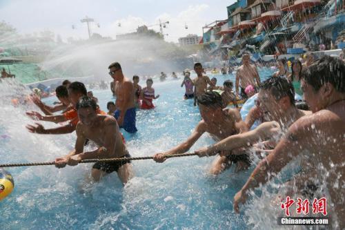 """质料图:上一年8月6日,重庆市形象台公布""""高温橙色预警灯号"""",局地达40℃。图为一水上乐园举行水中拔河角逐。 杨孝勇 摄"""