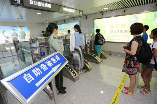 资料图片:2014年7月29日,中国旅客在青岛机场边检站自助通关。新华社发