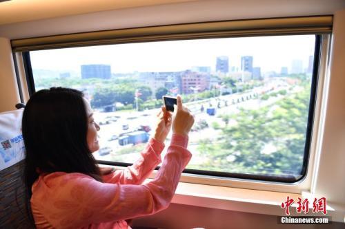 """图为""""复兴号""""高铁旅客拿手机拍摄窗外景色。中新社记者 陈文 摄"""