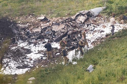 2018年2月10日,在以色列北部哈德福,安全人员在战机残骸旁警戒。新华社发
