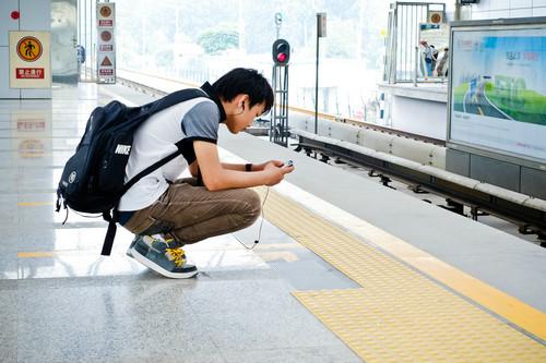 资料图片:2012年7月18日,在北京地铁立水桥站,一名年轻人在候车期间查看手机。新华社发