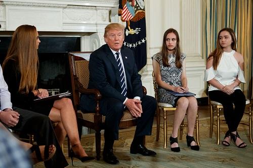 2018年2月21日,在美国华盛顿,美国总统特朗普(左二)在白宫会见了40多名经历过校园枪击案的学生、教师和学生家长,他承诺将加强对购枪者的背景审查,并表示考虑允许学校教职工配备枪支以防范校园枪击事件发生。新华社发(沈霆摄)。