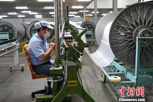 资料图:成都某玻纤制造厂忙碌的工人。 中新社记者 张浪 摄