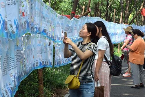 """资料图:一名市民在济南千佛山公园举行的""""七月七相亲大会""""上用手机记录相亲信息。 新华社记者 徐速绘 摄"""