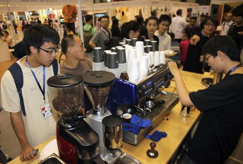 資料圖片:2011年6月18日,在2011北京國際咖啡博覽會上,工作人員現場烘焙咖啡。新華社發