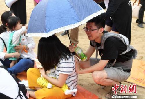 资料图:2017年5月,近200福州辣妈进行街头哺乳快闪活动,图为活动中一位丈夫帮妻子撑伞。 吕明 摄