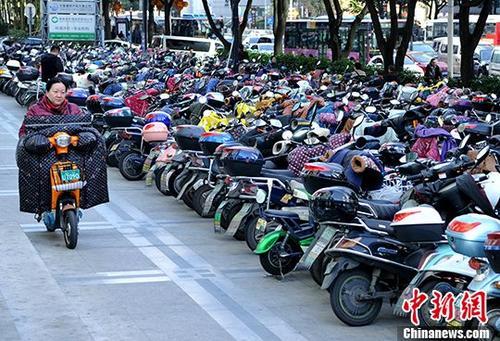 1月16日,福州市民从停车场骑电动车准备出行。 中新社记者 张斌 摄