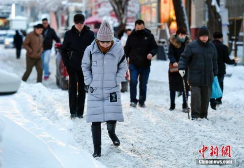 资料图:2017年12月28日,新疆乌鲁木齐降雪后,民众在雪中小心翼翼行走。中新社记者 刘新 摄