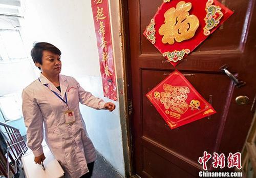 资料图:社区医生拎着便民医药箱前往附近居民家中回访巡诊。中新社记者 刘新 摄