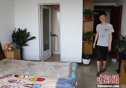资料图:台州玉环一名小伙展示自己通过当地租房平台找到的房子。中新社记者 王刚 摄
