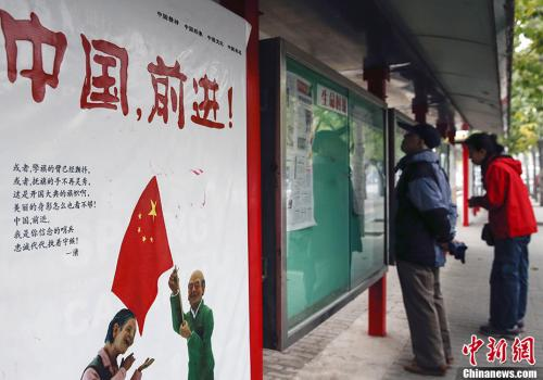 资料图:2013年11月13日,北京市民在一个阅报栏前关注十八届三中全会的新闻报道。中新社发 张浩 摄