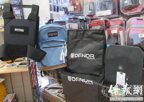 亚凯迪亚市枪店内的防弹背心、可放置防弹板的背包,以及做过枪击实验的防弹板。(吗,美国《侨报》记者翁羽摄)