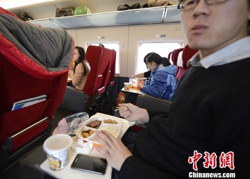 资料图:图为动车组乘客在品尝列车提供的餐食。中新社发 侯宇 摄
